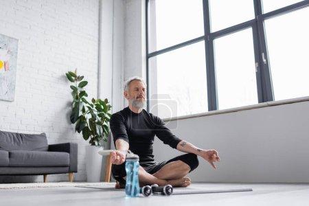 bearded man with grey hair meditating on yoga mat near dumbbells in living room