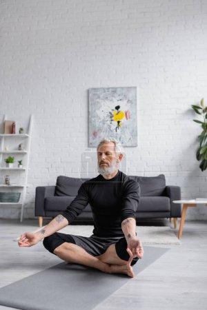 bearded man with closed eyes meditating on yoga mat near dumbbells