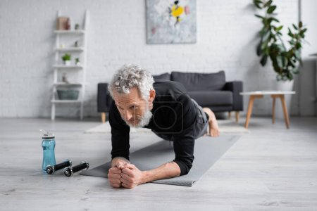 Photo for Bearded man with grey hair doing plank on fitness mat near dumbbells in living room - Royalty Free Image