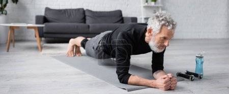 Photo for Barefoot man with grey hair doing plank on fitness mat near dumbbells in living room, banner - Royalty Free Image