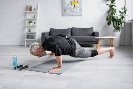 Photo for Barefoot man with grey hair working out on fitness mat near dumbbells in living room - Royalty Free Image