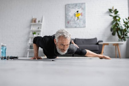 Photo for Strong man with grey hair working out on fitness mat near dumbbells in living room - Royalty Free Image