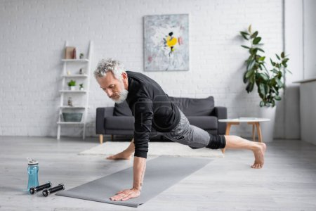 sportive man with grey hair working out on fitness mat near dumbbells in living room