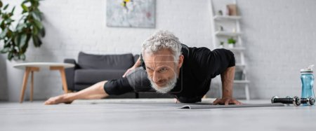 Photo for Strong man with grey hair working out on fitness mat near dumbbells in living room, banner - Royalty Free Image
