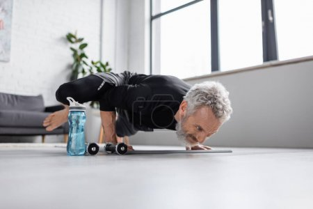strong man with grey hair exercising on fitness mat near dumbbells in living room