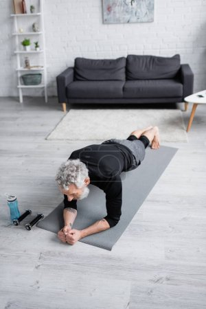 Photo for High angle view of man with grey hair exercising on fitness mat near dumbbells in living room - Royalty Free Image