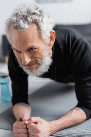 strong man with grey hair doing plank on fitness mat in living room