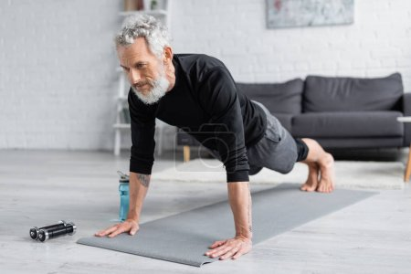 tattooed man with grey hair doing plank on fitness mat near dumbbells and sports bottle in living room