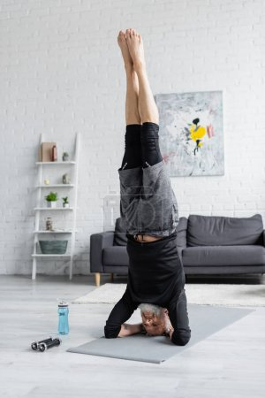 Photo for Strong man doing handstand on fitness mat near dumbbells and sports bottle in living room - Royalty Free Image