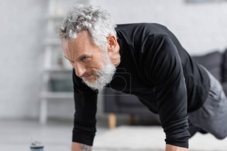 Photo for Strong and bearded man exercising in living room - Royalty Free Image