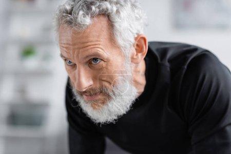 Photo pour Homme fort et barbu travaillant dans le salon - image libre de droit