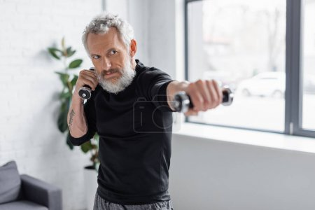 strong and bearded man working out with dumbbells in living room