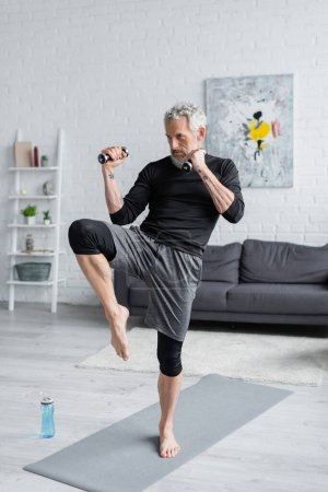 full length of strong and bearded man working out with dumbbells in living room