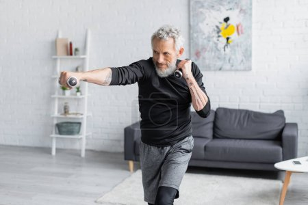 Photo for Tattooed and bearded man working out with dumbbells in living room - Royalty Free Image