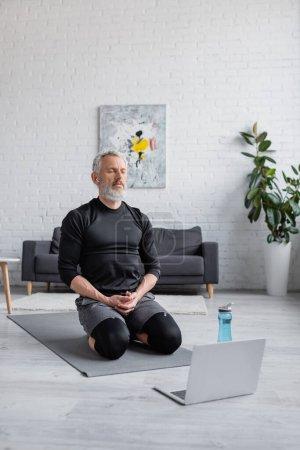 bearded man with grey hair listening music in wireless earphones near laptop in living room