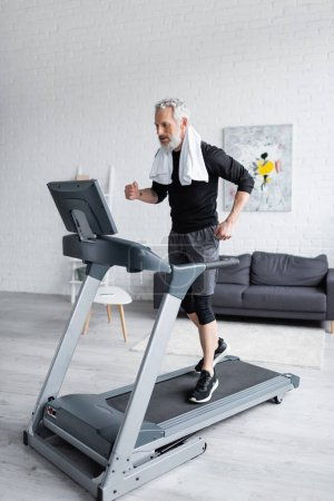 full length of bearded man with white towel jogging on treadmill at home