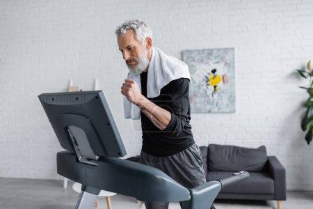 Photo pour Homme barbu mature avec serviette de course sur tapis roulant à la maison - image libre de droit