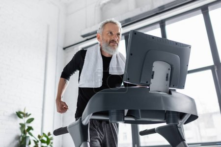 Photo pour Homme barbu avec serviette courir sur tapis roulant à la maison - image libre de droit