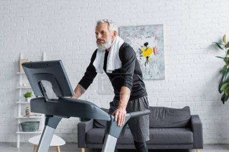 Photo pour Homme fatigué avec des cheveux gris et serviette d'exercice sur tapis roulant à la maison - image libre de droit