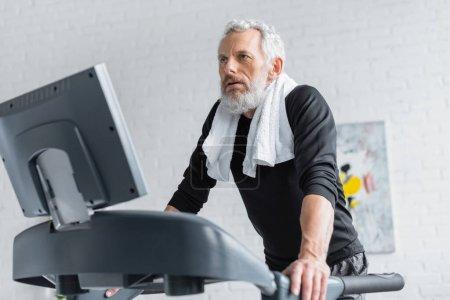 Photo pour Homme barbu avec les cheveux gris exercice sur tapis roulant à la maison - image libre de droit