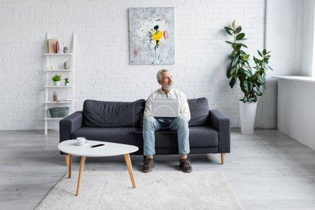 bärtiger Mann mit Laptop sitzt auf Couch neben Tasse Kaffee und Smartphone mit leerem Bildschirm auf Couchtisch
