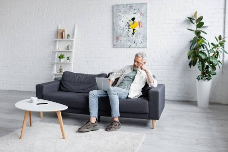 man with grey hair using laptop while sitting on couch near cup of coffee and smartphone with blank screen on coffee table
