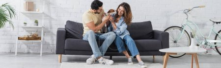 cheerful interracial couple petting jack russell terrier in modern living room, banner
