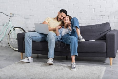 happy interracial freelancers sitting on sofa with laptop