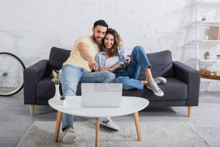 Photo for Happy muslim man pointing at laptop near smiling girlfriend on couch - Royalty Free Image