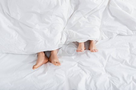 top view of barefoot couple under blanket lying on bed