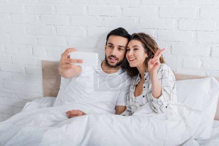 bärtiger muslimischer Mann macht Selfie, während glückliche Frau Friedenszeichen im Schlafzimmer zeigt