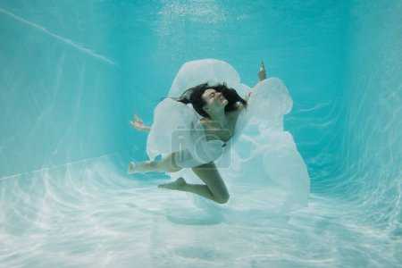 graceful young woman in white dress diving in pool