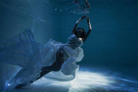 iluminación de la mujer tranquila en blanco elegante vestido de baño en la piscina