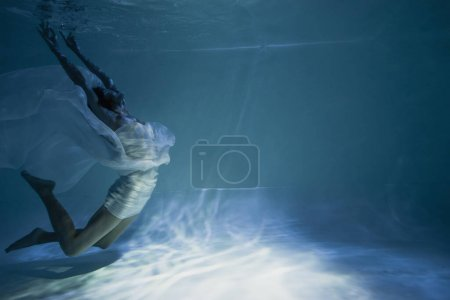 lighting near young graceful woman in white elegant dress swimming in pool with blue water