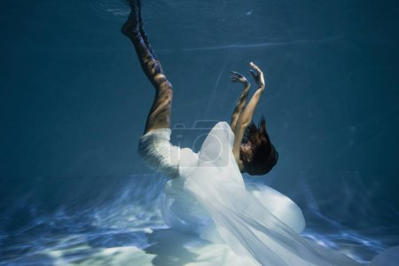 Photo for Lighting on young graceful woman in white dress diving in pool with blue water - Royalty Free Image