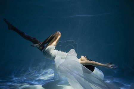 lighting on young woman in white dress diving in pool with blue water