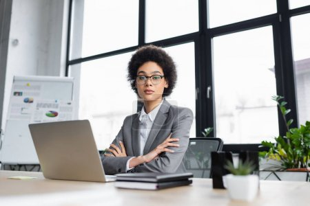 Photo for African american businesswoman with crossed arms sitting near laptop on table - Royalty Free Image