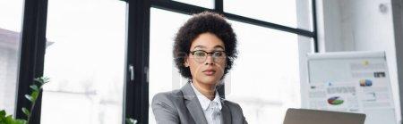 Photo pour Gestionnaire afro-américain regardant la caméra près d'un ordinateur portable dans le bureau, bannière - image libre de droit