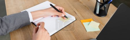 Cropped view of businesswoman writing on notebook with sticky note, banner