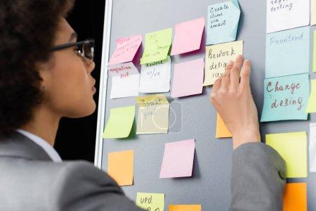 Photo pour Femme d'affaires afro-américaine floue regardant des notes collantes - image libre de droit
