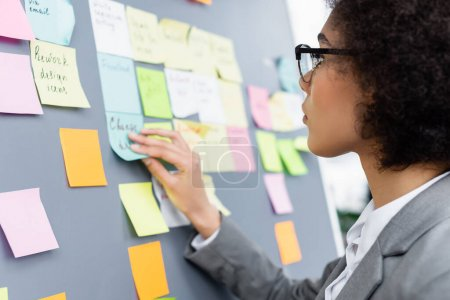 Young african american manager sticking blurred notes