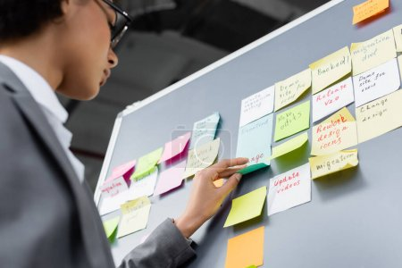 Photo for Low angle view of african american manager standing near board with sticky notes - Royalty Free Image