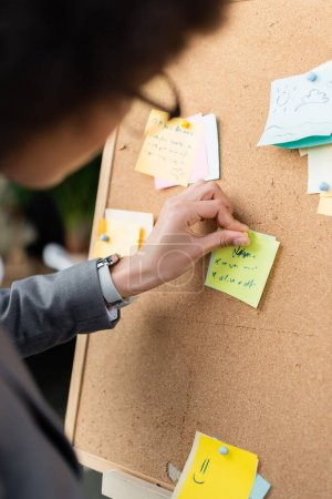 Blurred african american businesswoman attaching sticky note on board