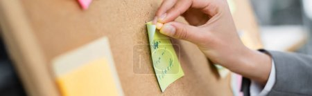 Cropped view of businesswoman attaching sticky notes on blurred board, banner