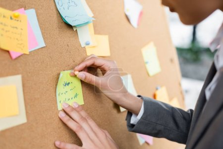 Cropped view of african american businesswoman attaching sticky note on blurred board in office