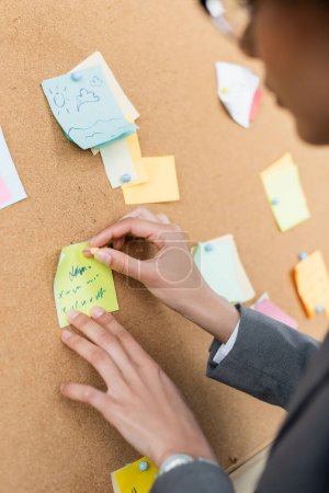 Cropped view of african american businesswoman attaching sticky note on wooden board