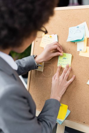 Blurred african american businesswoman holding pin and sticky notes