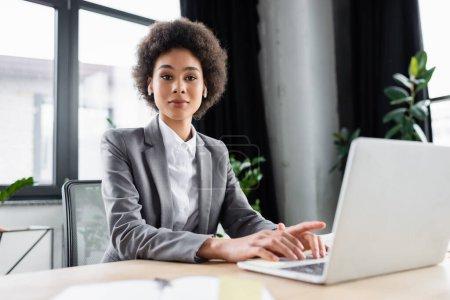 Foto de Mujer de negocios afroamericana en auriculares mirando la cámara cerca de la computadora portátil borrosa - Imagen libre de derechos