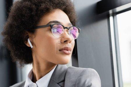 Joven mujer de negocios afroamericana en auricular de pie cerca de la ventana en la oficina