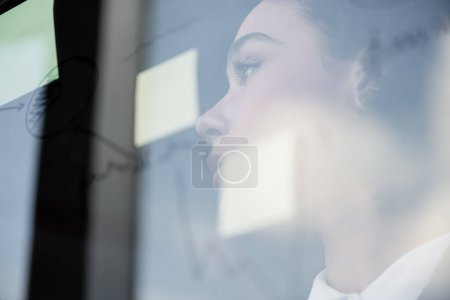 Photo for Side view of african american businesswoman standing near glass board with sticky notes - Royalty Free Image